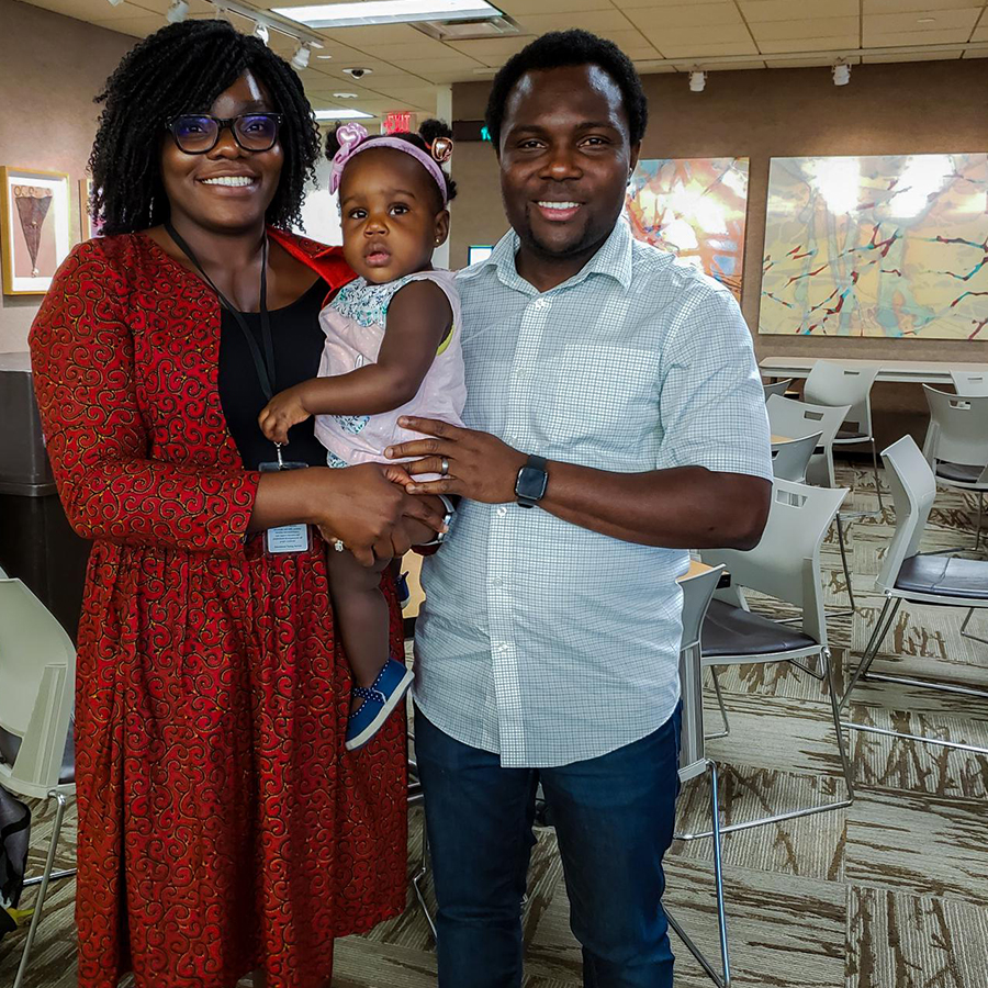Chioma, her husband, and their 1 year old all looking at the camera, the adults smiling, the baby looking confused.
